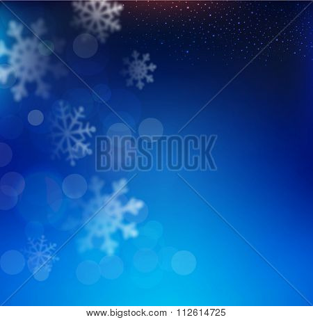 blue Christmas background with snowflakes blurred in the background
