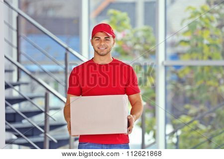 Delivery concept - postman in red uniform holding package near stairs