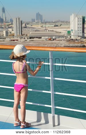 girl wearing swimming suit and hat is standing on deck of cruise ship