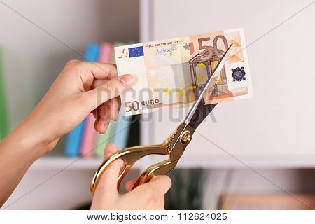 Hands with scissors cutting Euro banknote, on blurred interior background