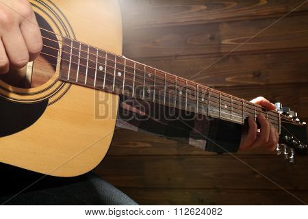 Guitarist plays guitar on wooden background, close up