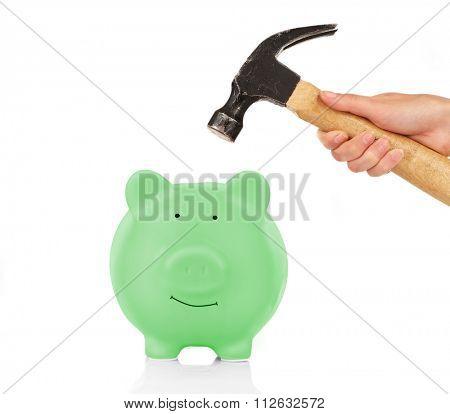 Female hand holding hammer above green piggy bank isolated on white