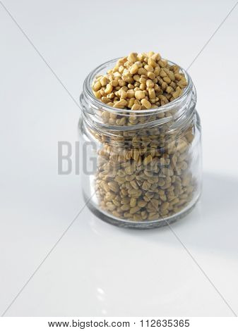 fenugreek in a glass container on white background