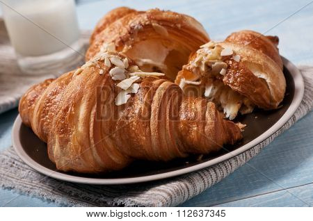 Croissant With Almonds On Blue Wooden Surface