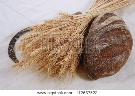 bunch of mown wheat ears with vintage handmade reaper hook sickle and rye dark french fresh bread loaf on white linen tablecloth
