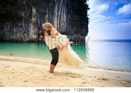 Groom Lifts Blonde Curly Bride In Fluffy Dress Holds On Beach