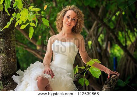 Blonde Bride In Fluffy Dress Sits On Trunk Groom Stands Near