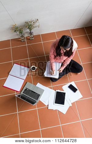 Top view of woman working at home with gadget