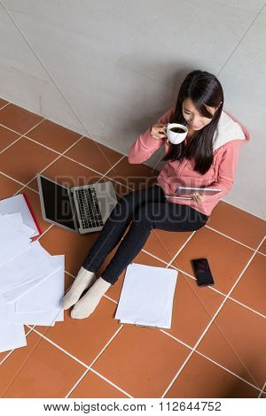Top view of woman working with laptop computer and drink of coffee