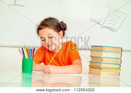 Pretty smart schoolgirl sitting at the desk in the classroom on blackboard background. Education.
