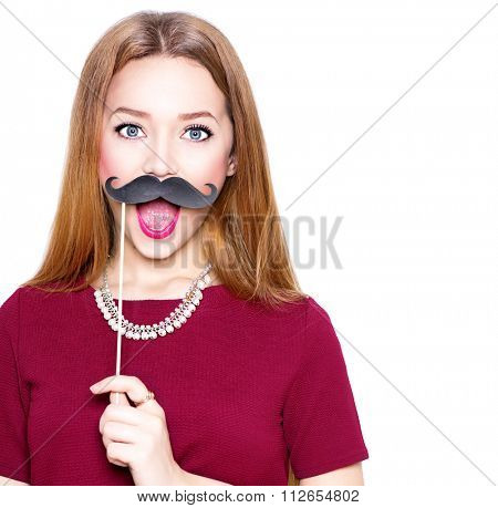 Surprised Teenage Gil holding funny mustache on stick. Joyful young woman ready for party, isolated on white background