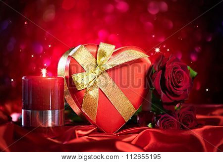 Valentine Red Heart Gift box and Red Rose Flower and flaming candle on Red Silk Background over glowing holiday background. St. Valentine's Day card design. Love