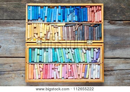 Multicolored Art Pastel Crayons In Open Wooden Artist Box On Table.