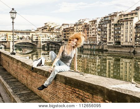 Young Joyful Woman Tossing Her Hair On The Wall In Front Of The Ponte Vecchio In Florence