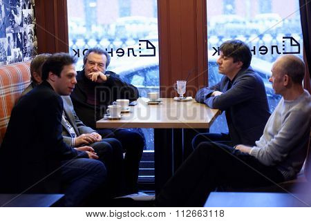 ST. PETERSBURG, RUSSIA - DECEMBER 16, 2015: Film director Alexey Uchitel (center left) and others in the cafe of the film studio Lendoc during 4th St. Petersburg International Cultural Forum
