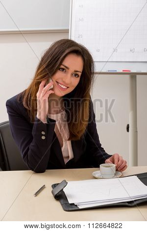 Business woman speaks on the phone.