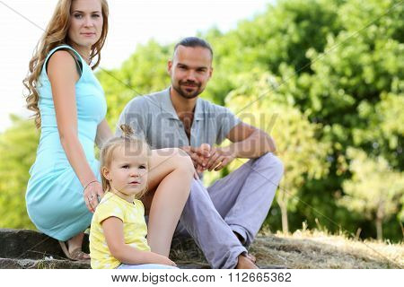 Young Parents With Daughter On Picnic Outdoor At Beautiful Sunny Day