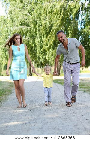Happy Parents With Daughter Outdoor Holding Her Hands