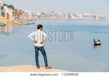 A man looking out of the river Ganges in Varanasi.