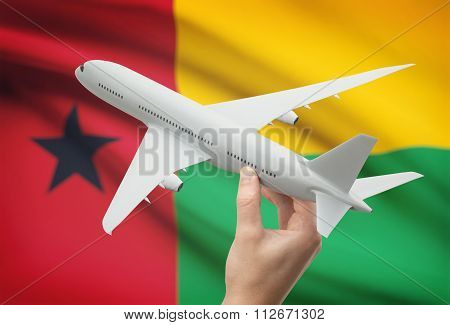 Airplane In Hand With Flag On Background - Guinea-bissau