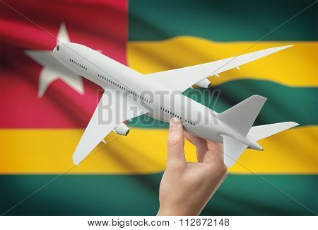 Airplane In Hand With Flag On Background - Togo