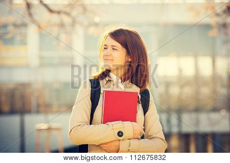 Young smiling student professional outdoors holding a red book freedom and serenity in campus