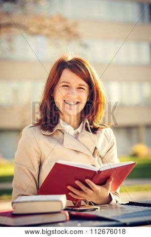 Happy student girl in campus holding a red journal