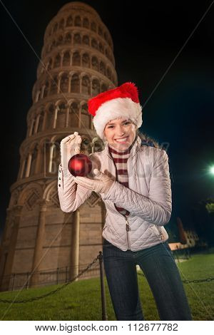 Happy Woman Showing Christmas Ball Near Leaning Tower Of Pisa