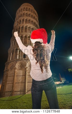 Woman In Santa Hat Rejoicing Near Leaning Tower Of Pisa, Italy
