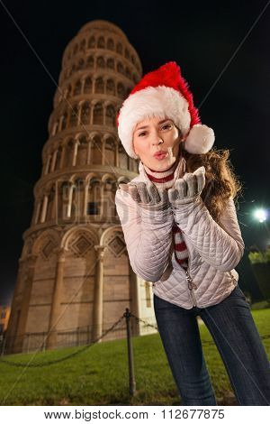 Woman In Santa Hat Blowing Air Kiss Near Leaning Tower Of Pisa