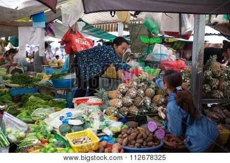 Vietnamese woman is selling fruits and vegetables at the wet market