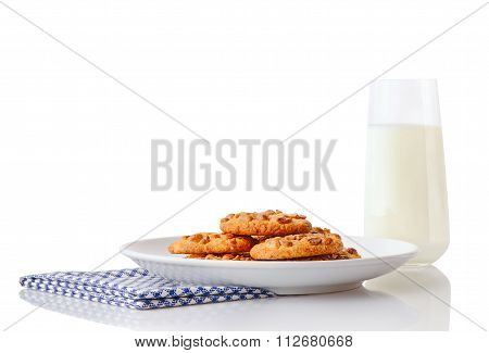 Pile of homemade peanut butter cookies on white ceramic plate on blue napkin and glass of milk