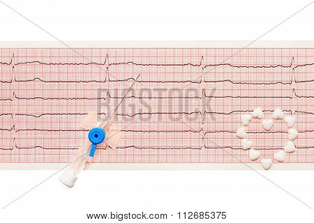 Heart made of white heart shape tablets and blue plastic catheter on paper ECG results