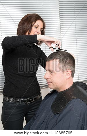 Female Hairdresser Cutting Hair Of Smiling Man Client