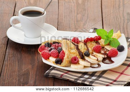 Crepes With Berries and cup of coffee.
