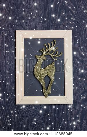 New Year's Background: A Deer Of Gold Color In A Photoframe On A Dark Wooden Covering.