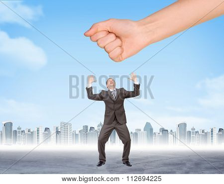 Hand trying to splash businessman
