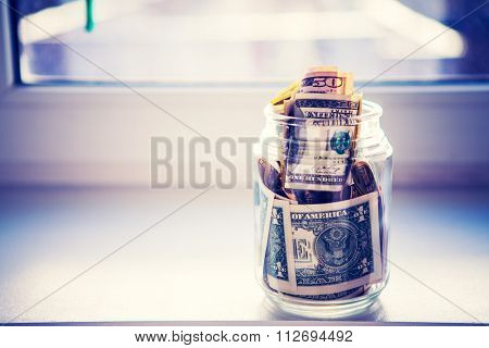 a glass jar with money is isolated on a background a window
