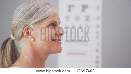 Mature woman receiving eyeglasses from optometrist