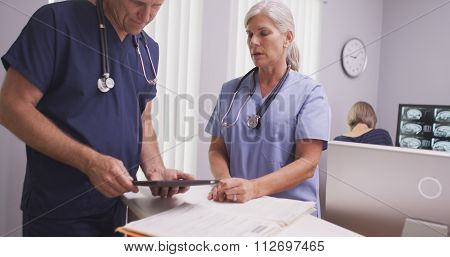 Mature female medical practitioner talking to male colleague at clinic desk