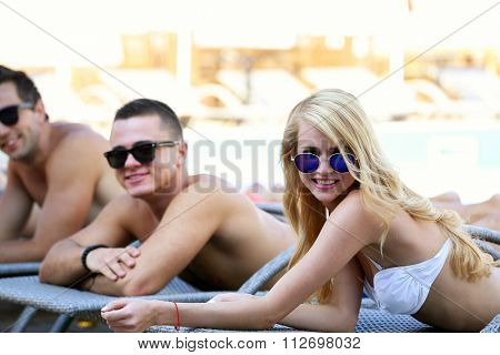 Young people relaxing on chaise-lounges
