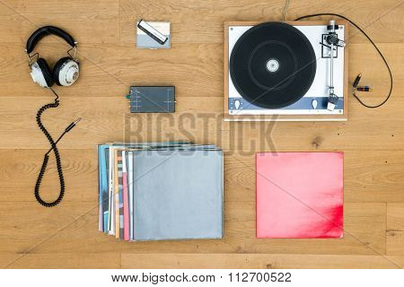 Directly above shot of turntable with records and headphones on wooden table