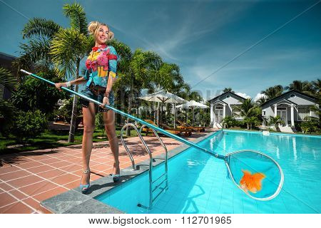 Female fishing with a net of the pool