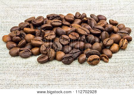 Pile Roasted Coffee Beans On Burlap, Close-up.