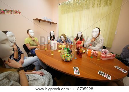 Seven young people play Mafia with masks at the table in the classroom