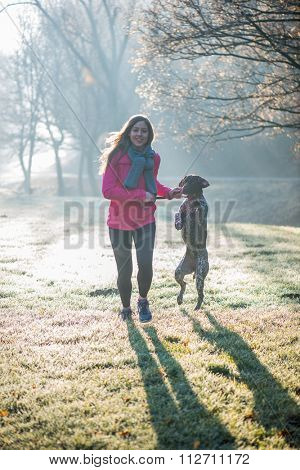Runner woman and her cute German pointer dog running together outdoor at the beautiful park. Healthy life concept.