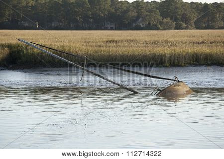 Sunken sailboat with mast out of the water