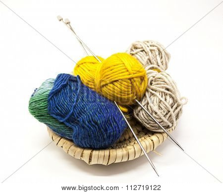 Three ball of woolen threads, yellow, blue, beige and steel knitting needles in a wooden basket on a white background