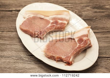 Pieces of fresh raw pork appetizing close-up on a white porcelain plate on a wooden background