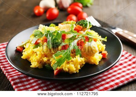 Black plate with vegetable risotto on served wooden table
